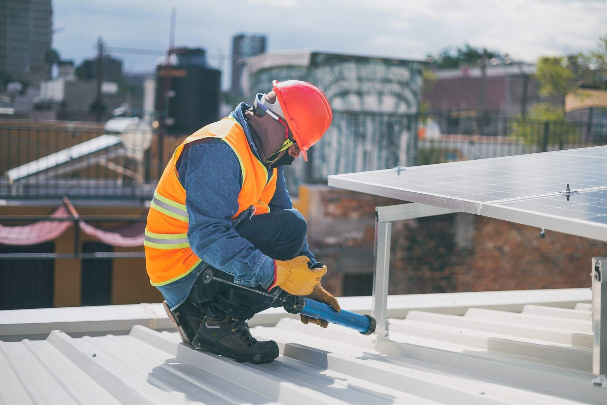 Construction worker installing solar panel on metal building roof