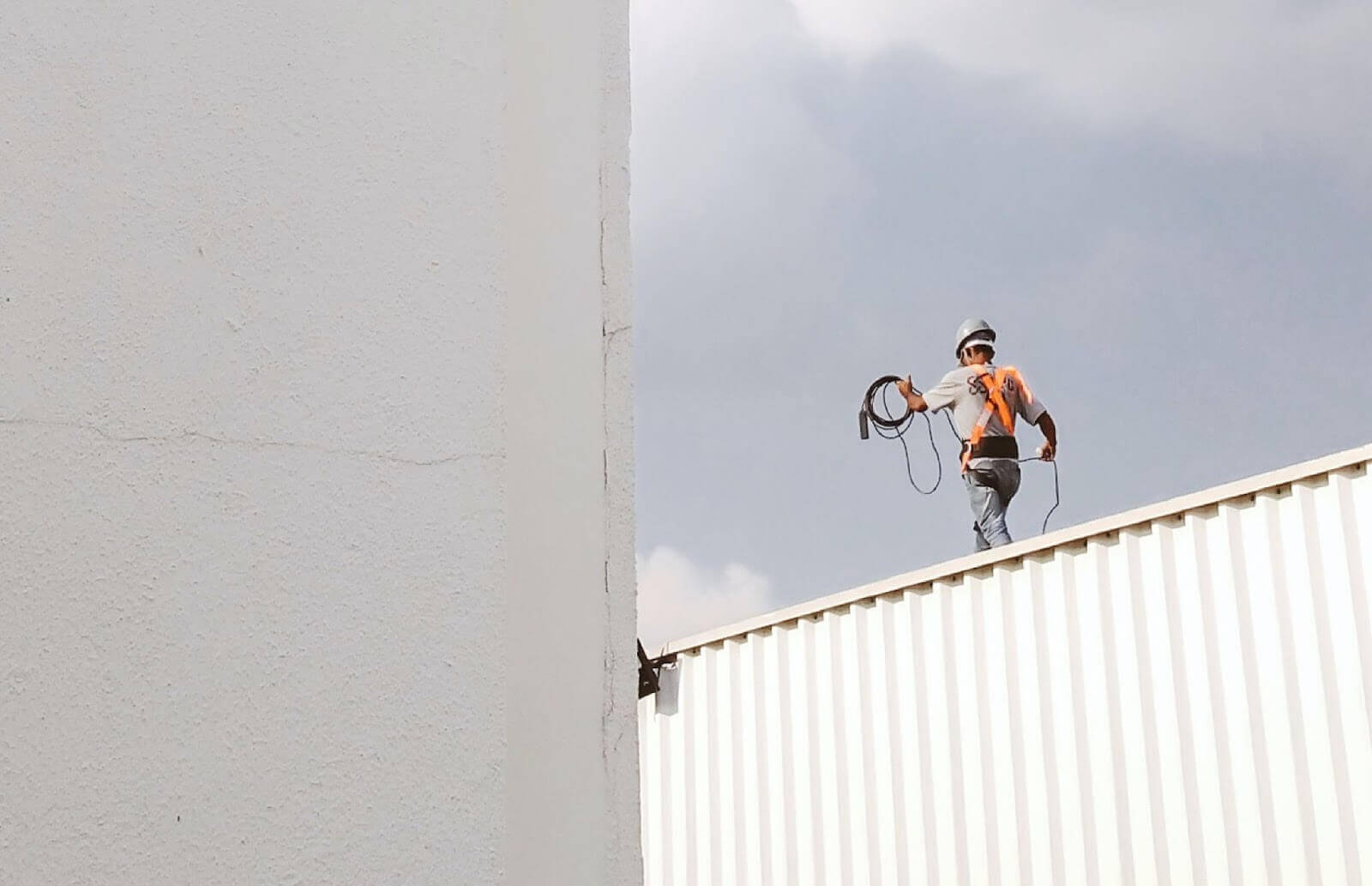 Construction worker walking on metal building roof