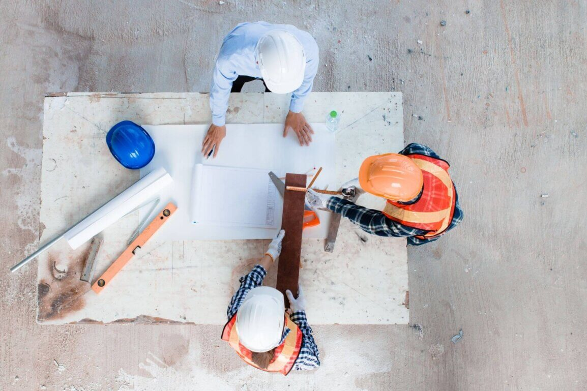 Birds-eye shot of four contractors wearing hard hats looking at blueprints on a table