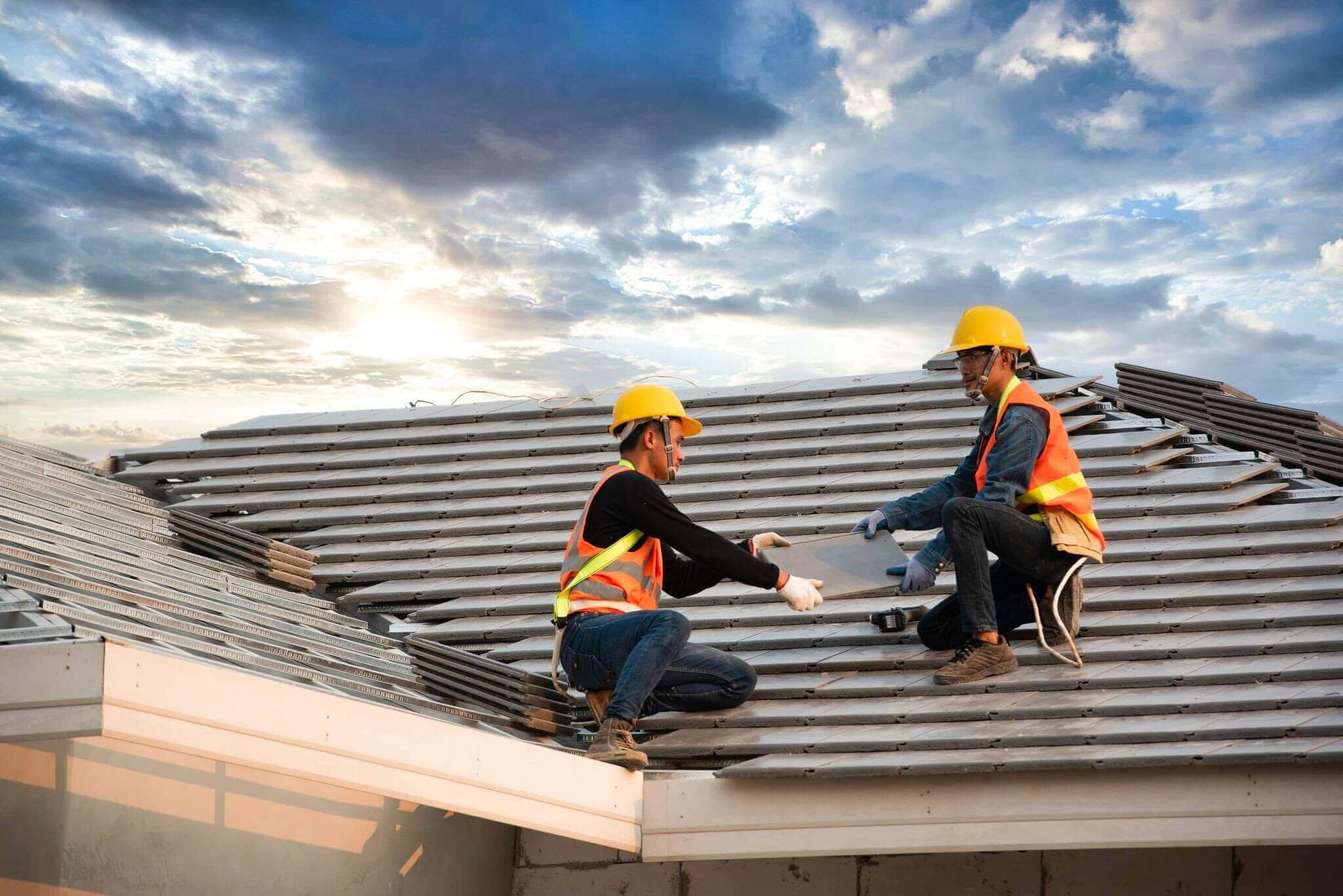 Two construction workers working on roof